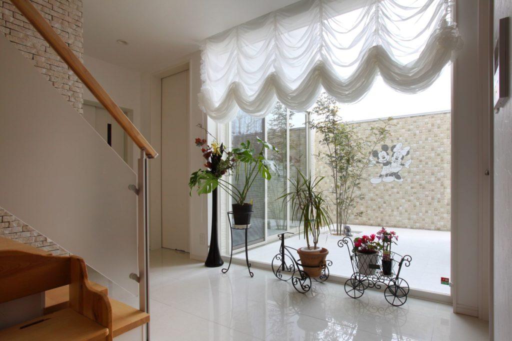 玄関正面に大開口の窓を設置し、明るいホールを実現