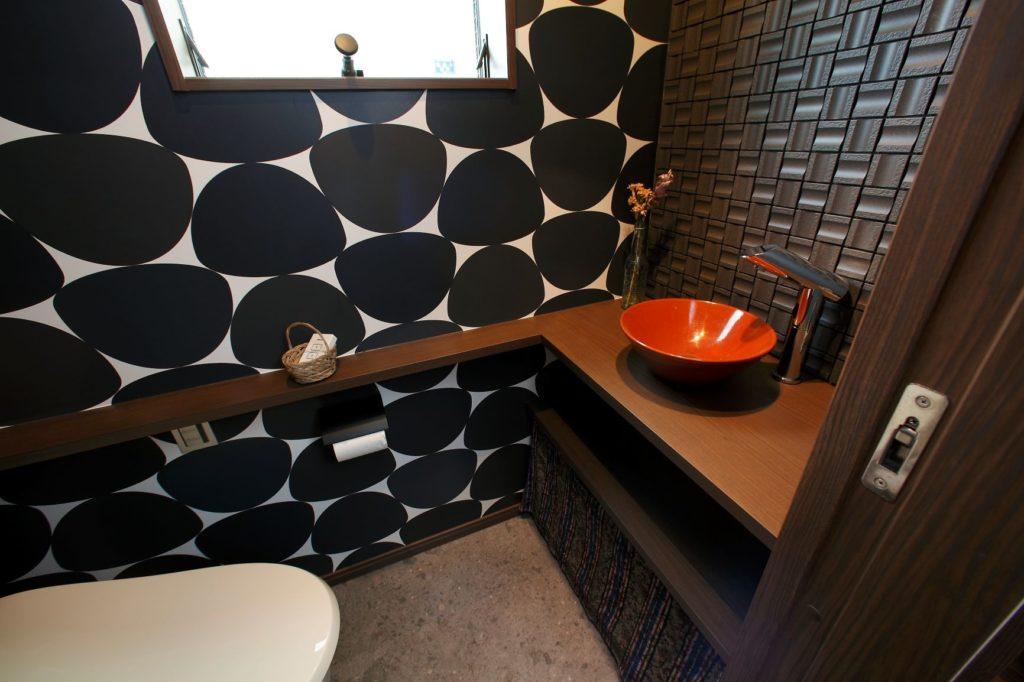 ドット柄のクロスやオレンジのシンクがかわいいトイレ