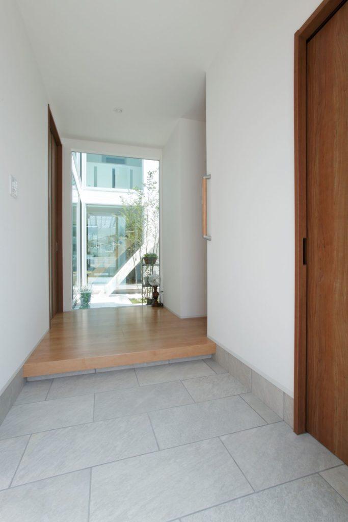 玄関に入ってすぐに中庭が見えるように大開口の窓を正面に設置