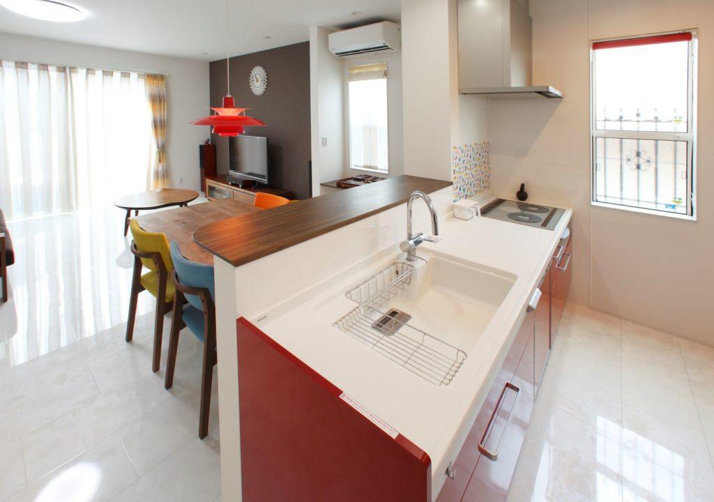 赤色のキッチンが特徴の開放的なキッチン